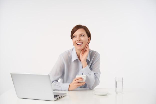 Goed uitziende jonge vrolijke bruinharige vrouw met kort trendy kapsel aanraken van haar nek met opgeheven hand en glimlachend gelukkig, poseren op wit met kopje thee Gratis Foto