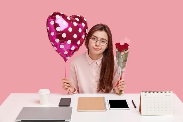 Goed uitziende vrouw heeft een attente blik, ontvangt aangename cadeautjes van vriend op kantoor, houdt valentijn ballon en rozen vast, draagt een bril Gratis Foto
