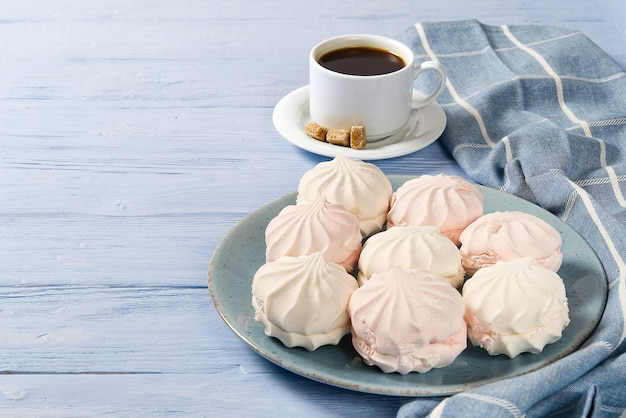 Goedemorgen banner. kopje koffie en zelfgemaakte dessert zefier, zefir op lichtblauwe houten tafel. bovenaanzicht. Premium Foto