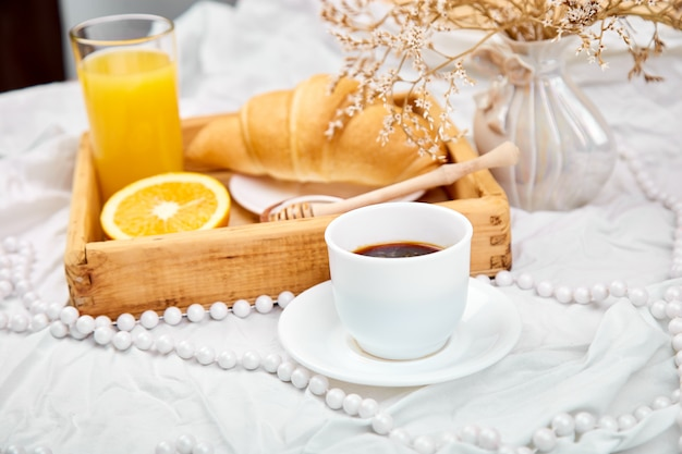 Goedemorgen. continentaal ontbijt op witte lakens. Premium Foto