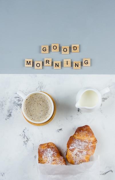 Goedemorgen ontbijt minimaal concept. kopje koffie, croissant en tekst good morning, plat leggen Premium Foto
