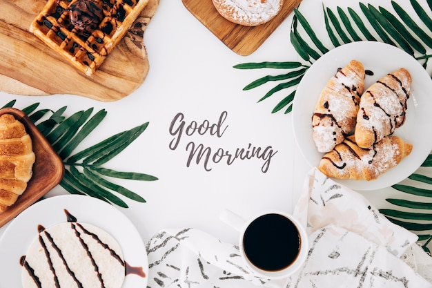 Goedemorgenbericht omringd met gebakken croissant; wafels; broodjes; tortilla's en koffie op witte achtergrond Gratis Foto