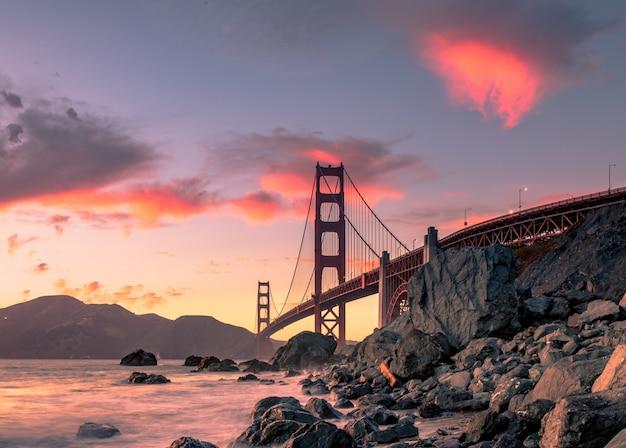 Golden gate bridge op watermassa dichtbij rotsvormingen tijdens zonsondergang in san francisco, californië Gratis Foto