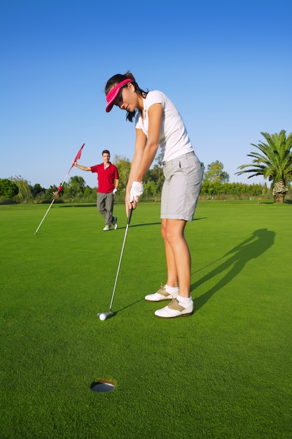Golf vrouw speler groene putting hole golfbal Premium Foto