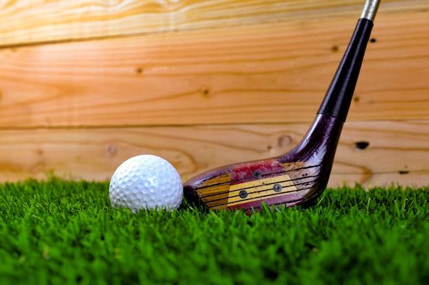 Golfbal en golfclub op gras met houten muur Premium Foto