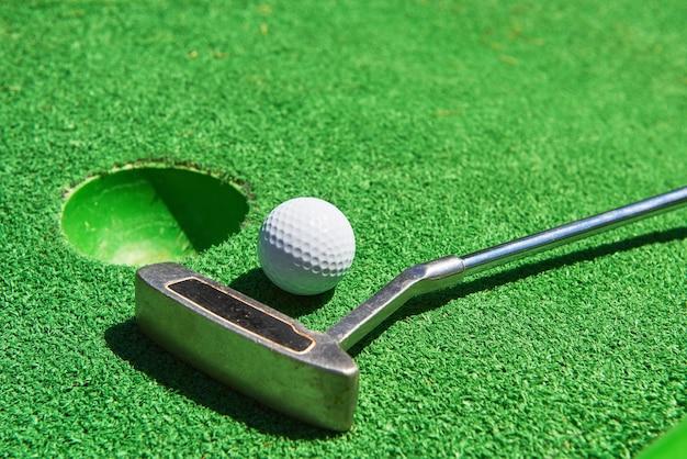 Golfbal en golfclub op kunstgras. Premium Foto