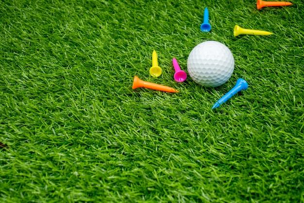 Golfballen en t-stukken zijn op groen gras. Premium Foto