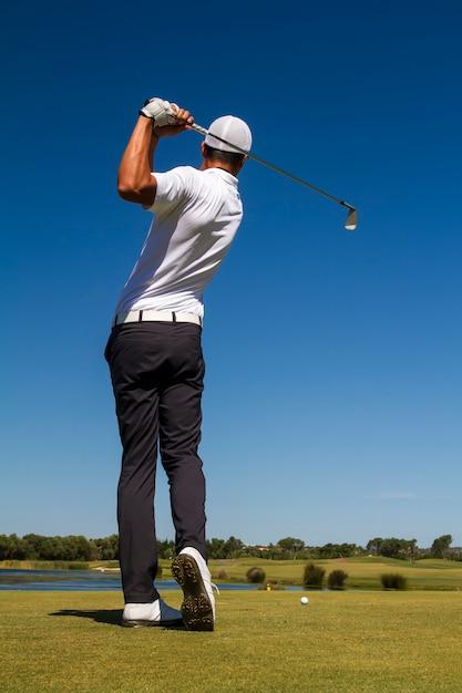 Golfspeler raakt een golfbal in een prachtige golfbaan. Premium Foto