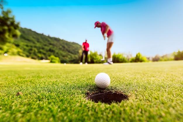 Golfspelerfocus die golfbal zetten in het gat tijdens zonsondergang, gezond en levensstijlconcept. Premium Foto