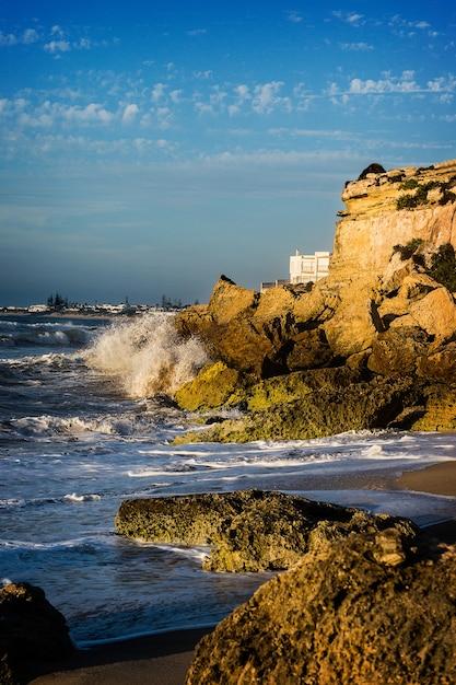 Golven die 's middags de klif in de kust van marokko raken Premium Foto