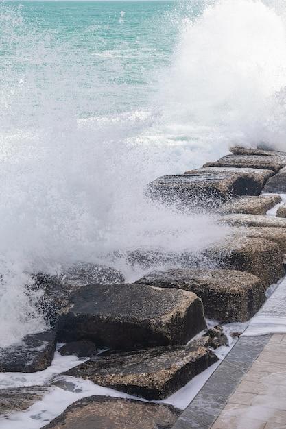 Golvende zee besprenkeling druppels op de stenen Gratis Foto