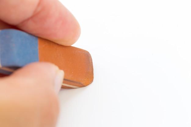 Gomhulpmiddel in een hand op wit wordt geïsoleerd dat. school en kantoor tool Premium Foto