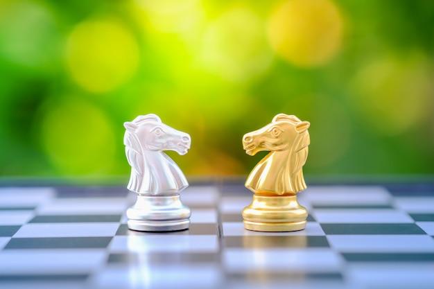 Goud en zilver schaken ridder stuk op schaakbord. Premium Foto
