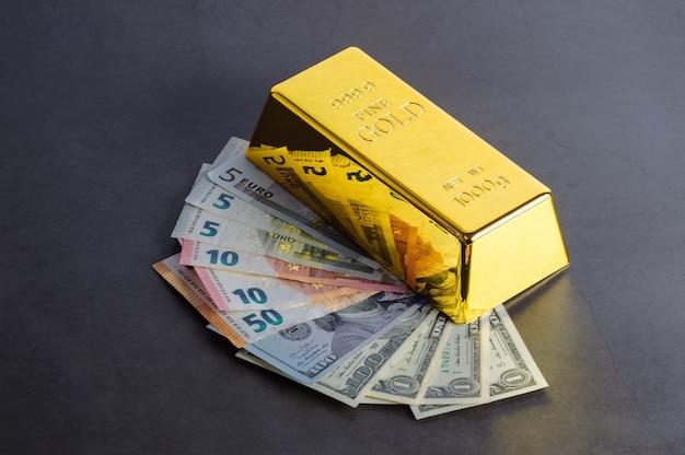 Goud staaf baar bullion tegen de achtergrond van de dollar en de euro rekeningen. Premium Foto