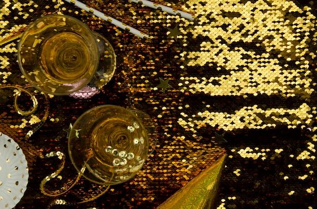 Gouden achtergrond met champagneglazen bovenaanzicht Gratis Foto