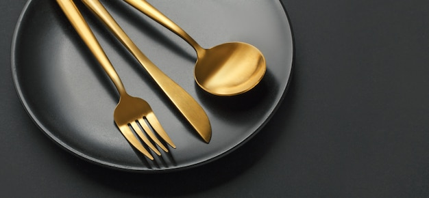 Gouden bestek ingesteld op zwarte achtergrond Gratis Foto