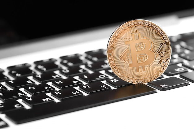 Gouden bitcoin op computertoetsenbord, close-up. bitcoins en virtueel geld Premium Foto