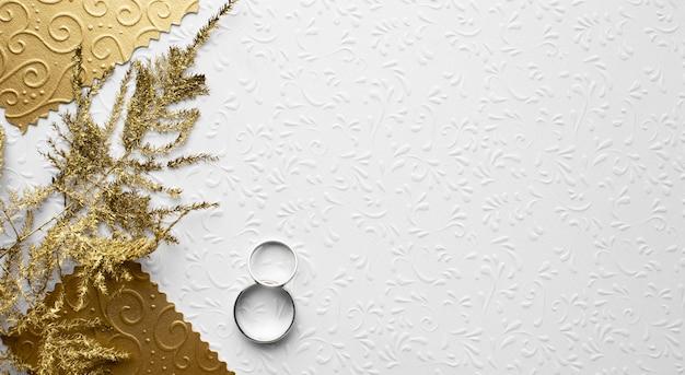 Gouden bladeren en ringen bewaren het concept van het datumhuwelijk Gratis Foto