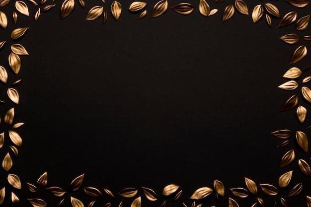Gouden bladeren op zwarte achtergrond exemplaarruimte Gratis Foto