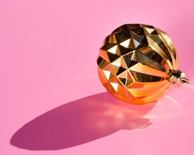 Gouden bol op roze achtergrond Gratis Foto