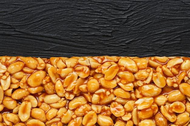 Gouden boletus kozinaki van geroosterde pindabonenergierepen. zwarte textuur achtergrond, bovenaanzicht Premium Foto