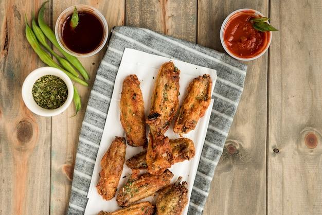 Gouden bruine geroosterde kippenvleugels en sausen Gratis Foto