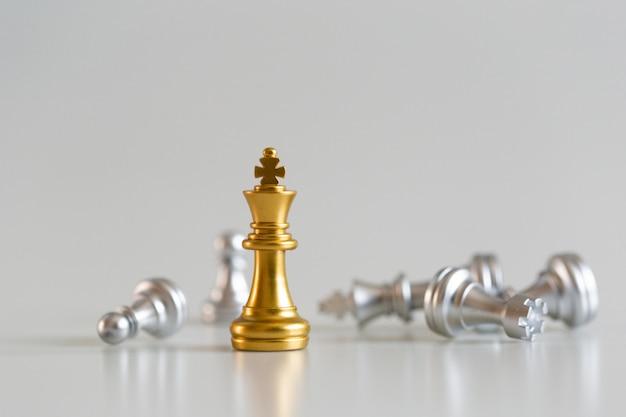 Gouden de koning van het schaakspel status en zilveren achtergrond, bedrijfsstrategieconcept. Premium Foto