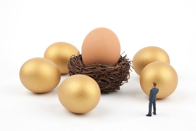 Gouden eieren en bedrijfsmens op witte achtergrond Premium Foto