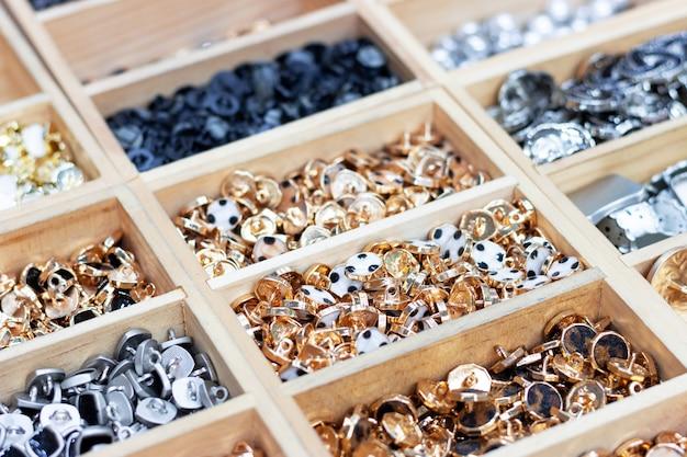 Gouden en zilveren knopen liggen in houten gleuven, een zijaanzicht Premium Foto