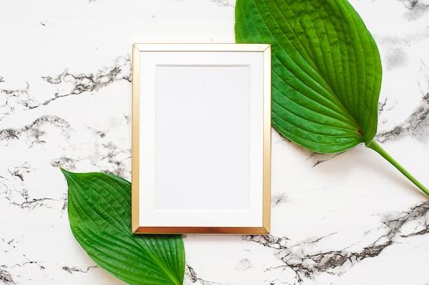 Gouden fotolijst met tropische bladeren op marmeren achtergrond. mock-up frame Premium Foto