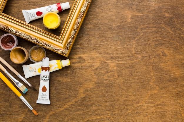 Gouden frame met verf en borstels Gratis Foto
