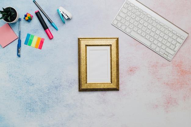 Gouden frame op bureaublad voor mock up Gratis Foto