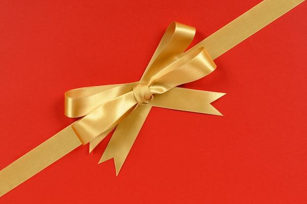 Gouden geschenk lint hoek diagonaal geïsoleerd op rode achtergrond inwikkeling papier Gratis Foto