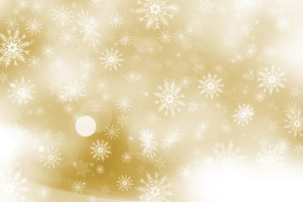 Gouden kerstmisachtergrond met sneeuwvlokken en sterrenontwerp Gratis Foto