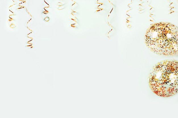 Gouden kronkelige vakantiedecoratie en ballons met kleurrijke confettien op lichte achtergrond Premium Foto