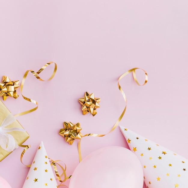 Gouden lintboog; streamers; geschenkdoos; ballonnen en feestmuts op roze achtergrond Gratis Foto