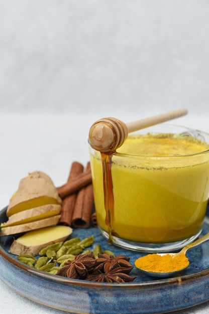 Gouden melk in glaskop met kruiden over dichte omhooggaand. honing stroomt in een kopje. Premium Foto