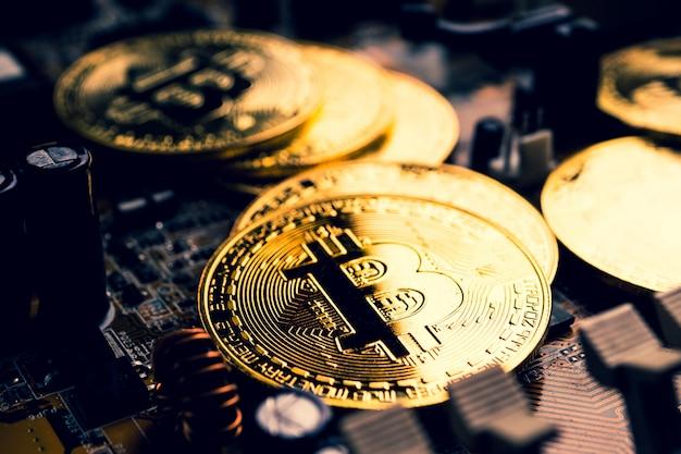 Gouden munten met bitcoin symbool op een moederbord. Premium Foto