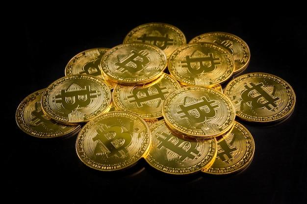 Gouden munten met bitcoin symbool op een zwarte achtergrond. Premium Foto