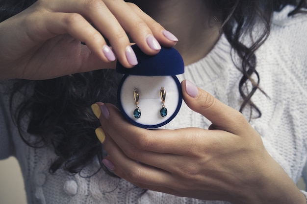 Gouden oorringen met blauwe topaas in de handen van vrouwen Premium Foto