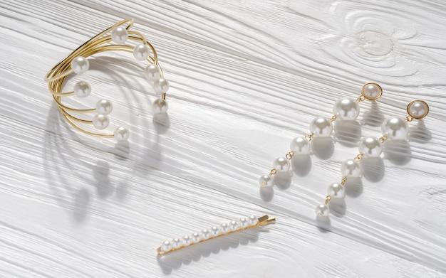Gouden parel en gouden set armband, oorbellen paar en haar pin op witte houten achtergrond Premium Foto