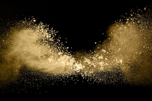 Gouden poeder explosie op zwarte achtergrond. Premium Foto