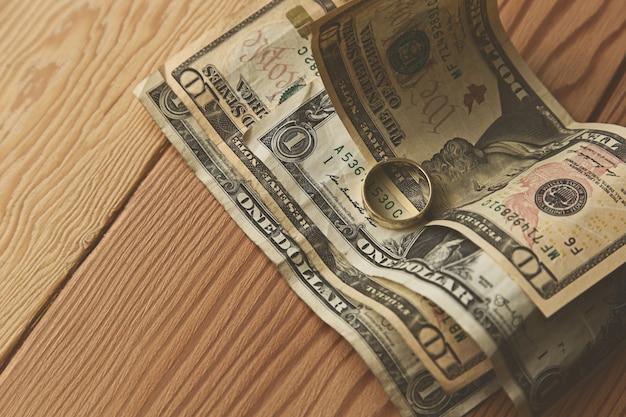 Gouden ring op sommige dollarbiljetten op een houten oppervlak Gratis Foto