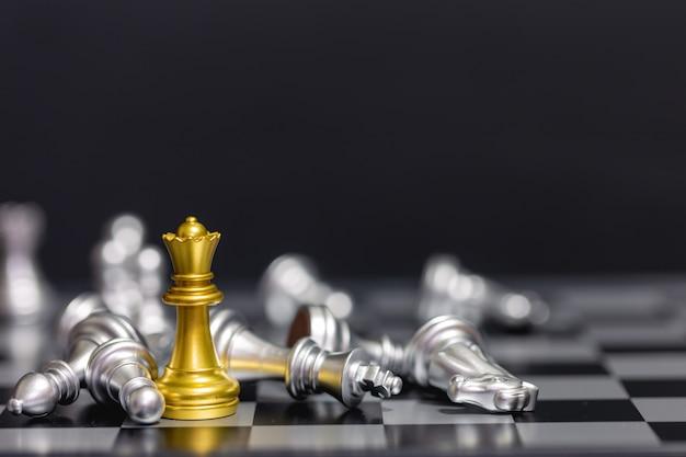 Gouden schaakstukken verslaan het zilveren schaakteam op een zwarte achtergrond Premium Foto