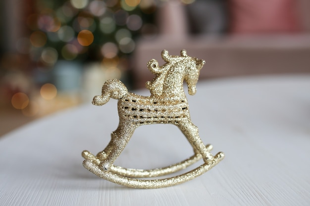 Gouden speelgoed decor paard staande op de tafel tegen de achtergrond van een boom bokeh en slingers Premium Foto