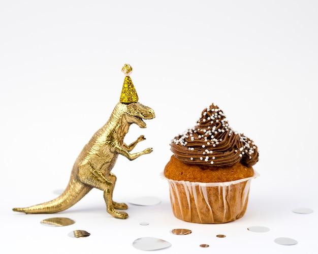 Gouden speelgoed dinosaurus en smakelijke muffin Gratis Foto