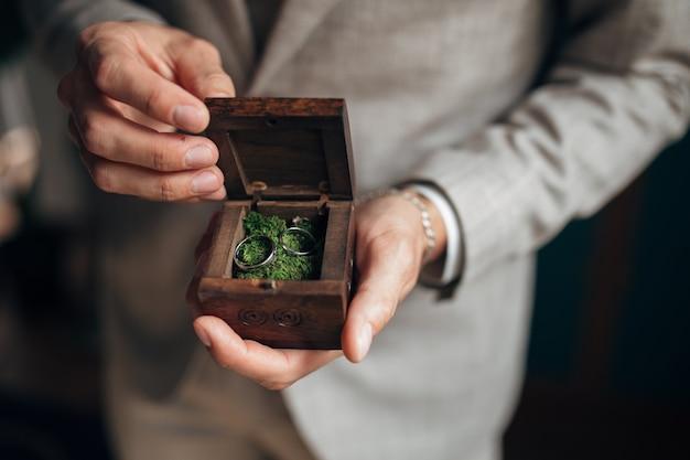 Gouden trouwringen in de handen van de bruidegom Premium Foto