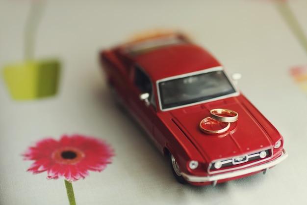Gouden trouwringen liggen op een speelgoed rode mustang Gratis Foto