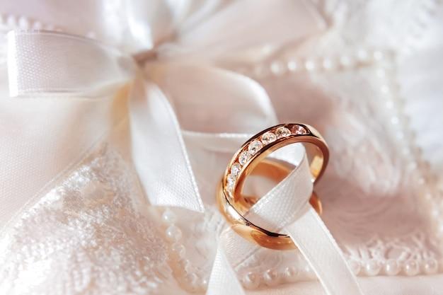 Gouden trouwringen met diamanten op stof. bruiloft sieraden details. verlovingsring met kostbare edelstenen. Premium Foto
