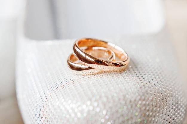 Gouden trouwringen op bruidschoenen met bergkristallen. bruiloft sieraden details. symbool van liefde en huwelijk. Premium Foto